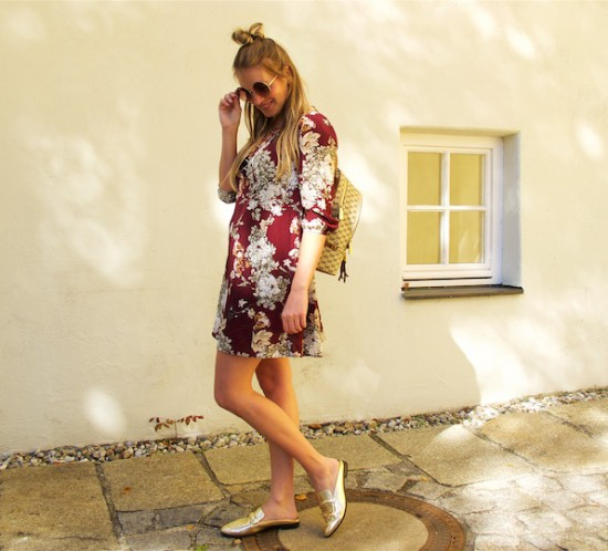 Burgundy Flower Dress. Fashion Blogger Girl by Style Blog Heartfelt Hunt. Girl with blond half-up half-down bun wearing a burgundy flower dress, round sunglasses, Michael Kors backpack and mules.