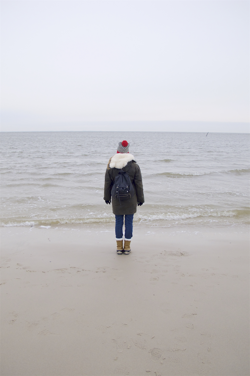 Christmas Vacation On The North Sea. Fashion and Style Blog Girl from Heartfelt Hunt. Girl with blonde, long hair wearing a Barbour coat, teddy coat, red turtleneck sweater, Levi's jeans, beanie with pompom, backpack and Sorel boots.