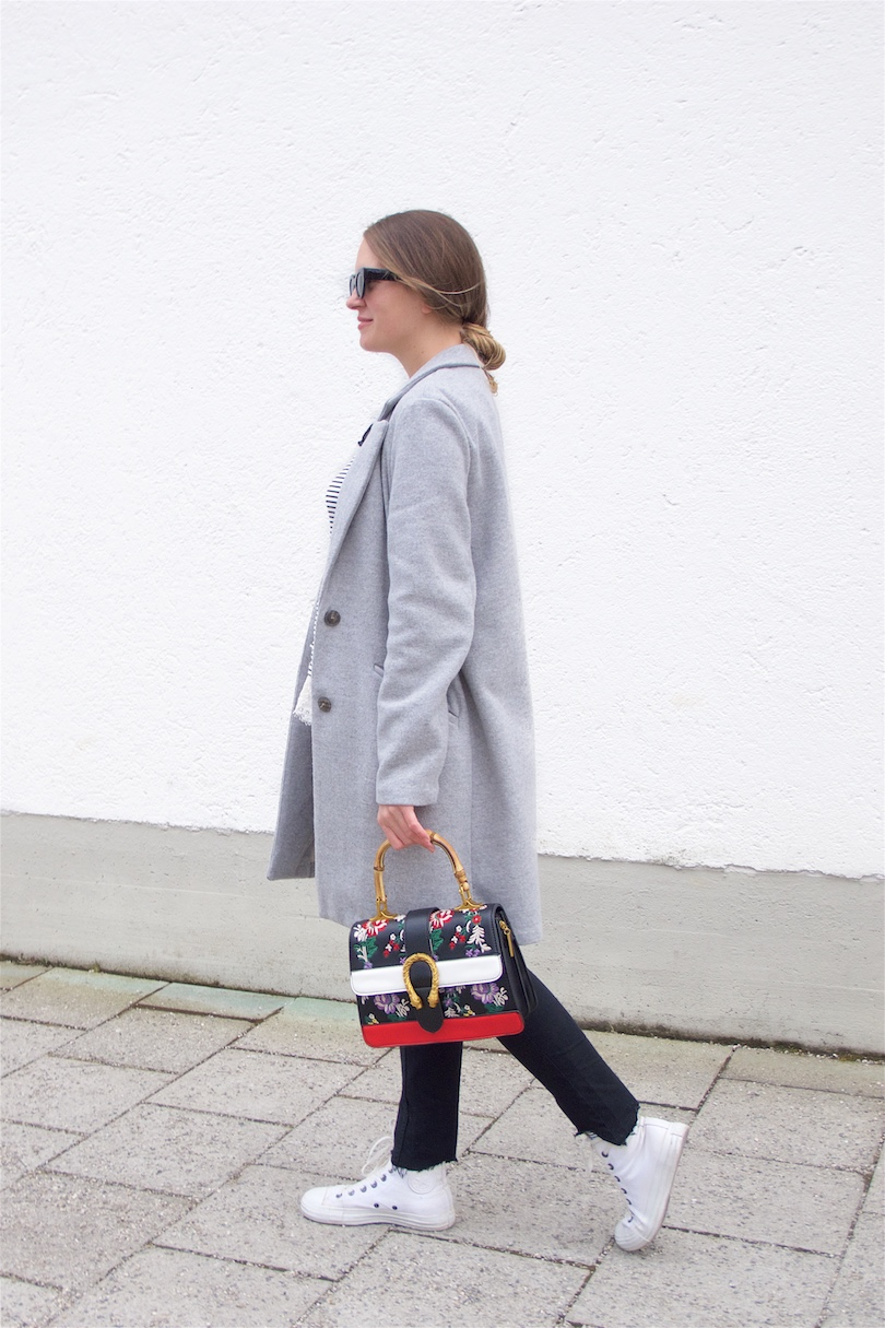 Embroidered Bag. Fashion and Style Blog Girl from Heartfelt Hunt. Girl with blonde, low messy bun wearing a gray coat, striped top, lace top, jeans, sunglasses, embroidered bag and Converse sneakers.
