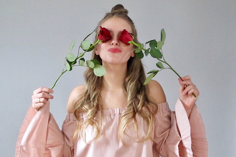 Happy Valentines Day. Fashion Blogger Girl by Style Blog Heartfelt Hunt. Girl with blond, loose curls and half-up half-down bun wearing a light pink off shoulder blouse with ruffled sleeves.