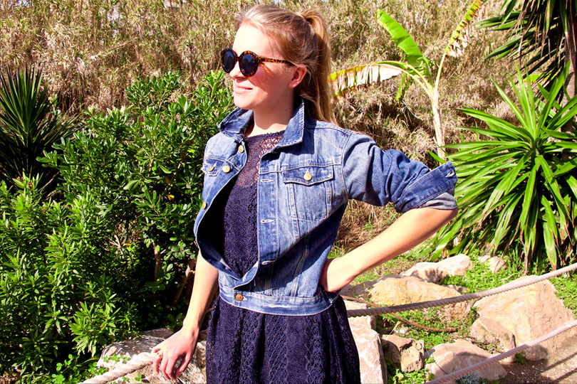 Smiling blond fashion and style blogger girl with high ponytail wearing a dark-blue lace dress, denim jacket and sunglasses