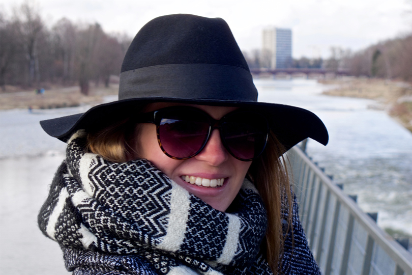 Smiling blond fashion and style blogger girl in closeup view wearing an oversized jacket, black hat, sunglasses and a black and white scarf