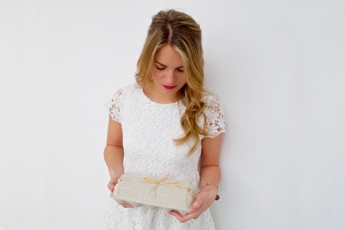 Blonde fashion and style blogger girl in closeup view holding an egg carton with a bow, wearing a romantic, white lace dress and red lipstick