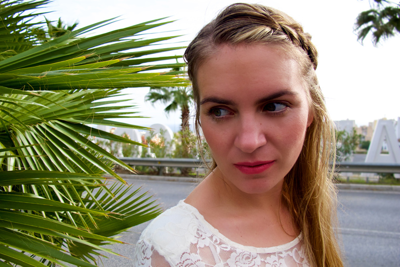 Blonde fashion and style blogger girl in closeup view with braided half-up half-down hairstyle and lace top