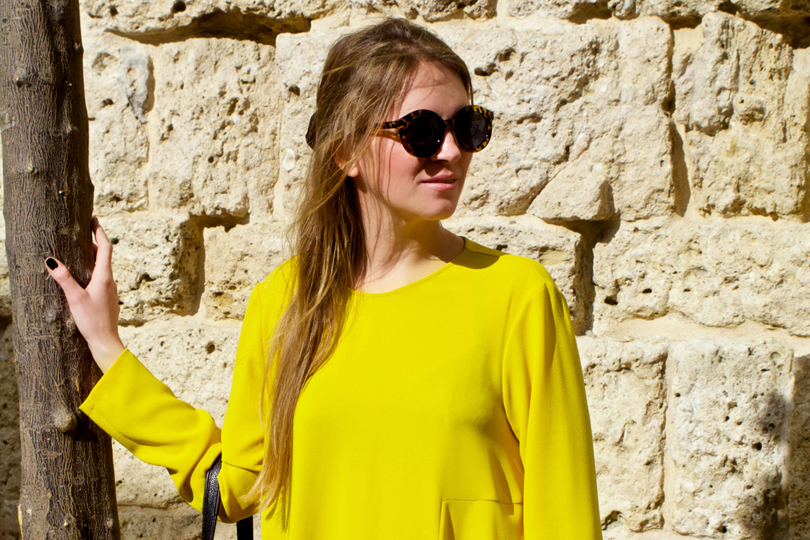 Smiling blonde fashion and style blogger girl wearing a colorful, yellow dress and sunglasses in the beautiful old town of Marbella