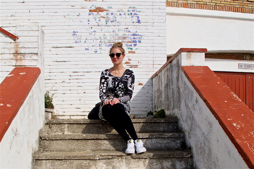 Blonde fashion and style blogger girl sitting on stairs, wearing a lace dress, Michael Kors bag, Rayban sunglasses and adidas sneakers