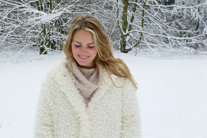 Smiling blonde fashion and style blogger girl in closeup view wearing a teddy bear coat with hood in a winter wonderland