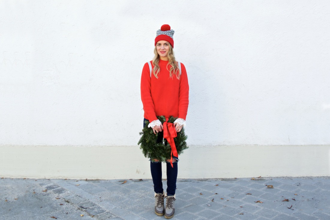 Holiday Wreath. Fashion Blogger Girl by Style Blog Heartfelt Hunt. Girl with blond, loose curls wearing a red sweater, lace top with bell sleeves, destroyed jeans, pompom beanie, backpack and boots.