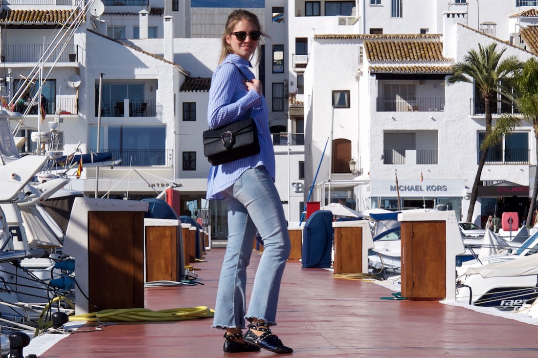 Maritime Stripes. Fashion Blogger Girl by Style Blog Heartfelt Hunt. Girl with blond, long hair wearing a blouse in maritime stripes, cropped flare jeans, Ray-Ban sunglasses, bag and lace up ballet flats.