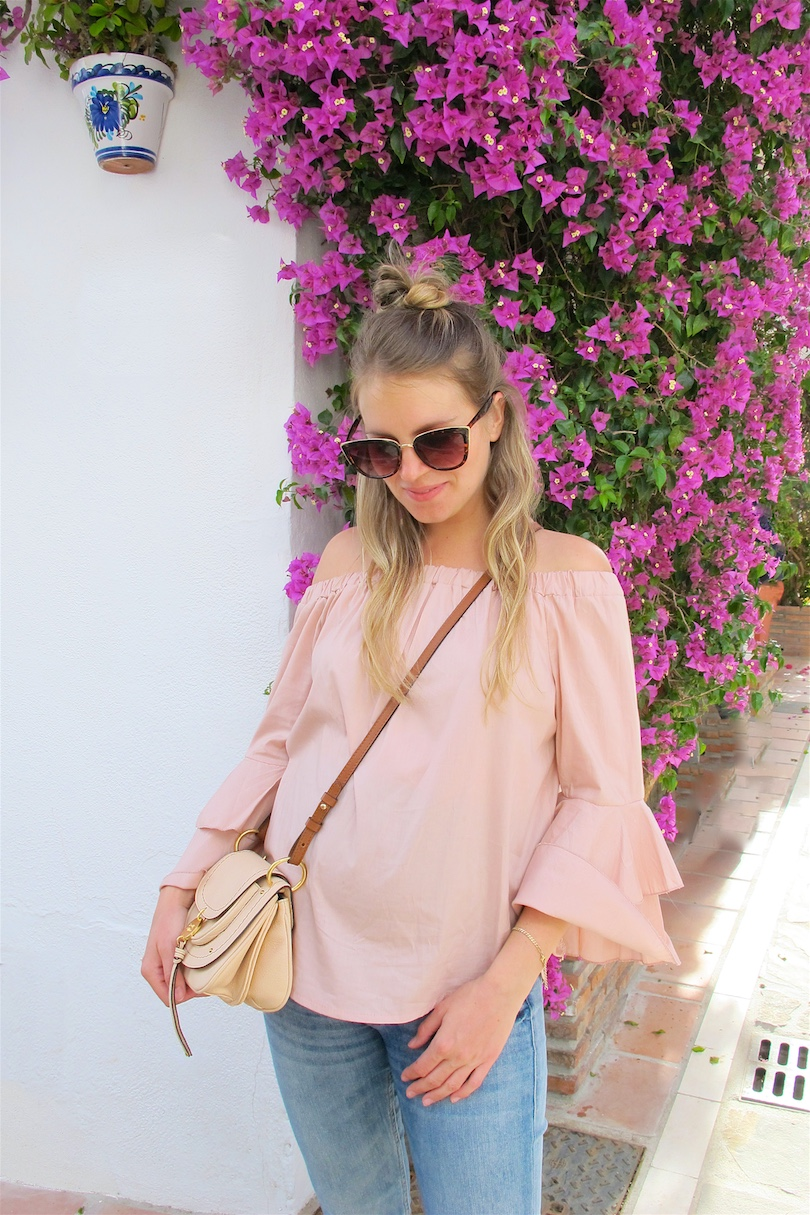 Nude Blouse With Ruffled Sleeves. Fashion and Style Blog Girl from Heartfelt Hunt. Girl with blonde half-up half-down bun wearing a nude off-shoulder blouse with ruffled sleeves, jeans, cat eye sunglasses, See by Chloé bag and lace up sandals.