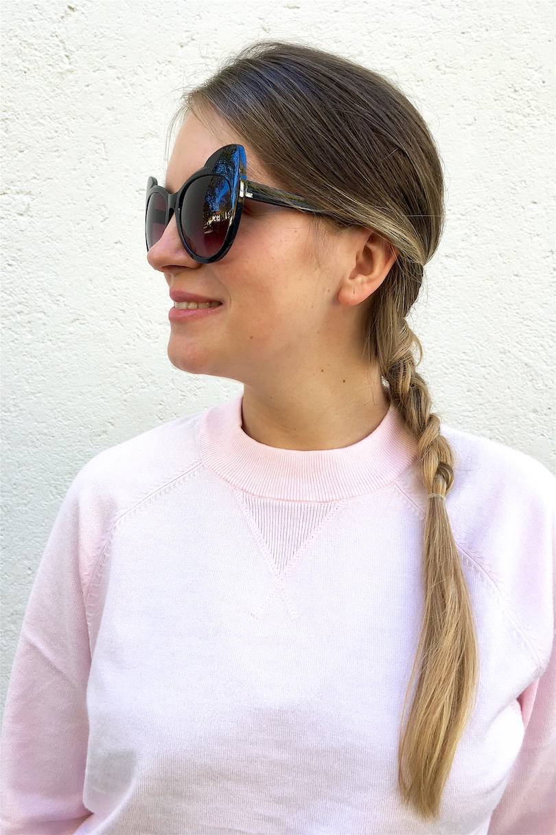 Pink Sweater. Fashion and Style Blog Girl from Heartfelt Hunt. Girl with blonde dutch braid wearing a black dress, pink sweater, Michael Kors bag, cat eye sunglasses and mule sneakers with a bow.