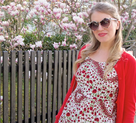 Red & Blush. Fashion Blogger Girl by Style Blog Heartfelt Hunt. Girl with blond half-up half-down bun wearing a red cardigan, floral dress, blush bag, scarf and velvet loafers.