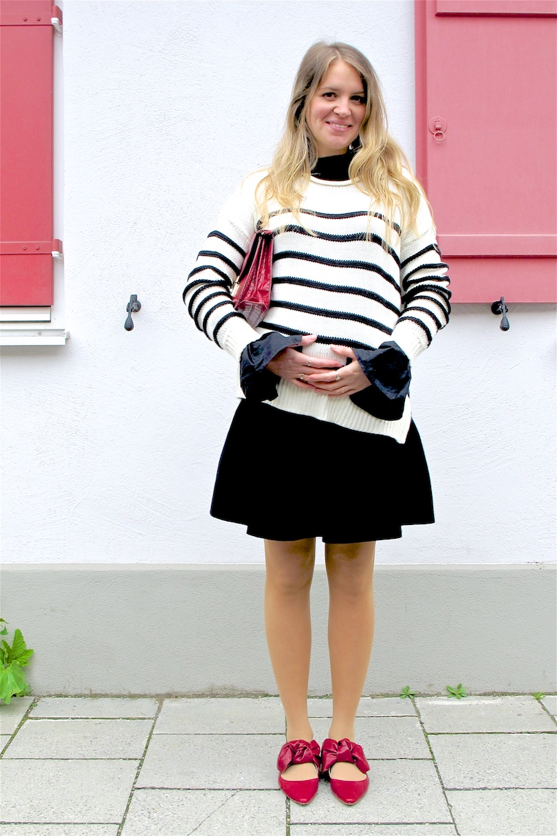 Red Bow Shoes. Fashion Blogger Girl by Style Blog Heartfelt Hunt. Girl with blond, loose curls wearing red bow shoes, striped sweater, top with trumpet sleeves, flared skirt and a red bag.