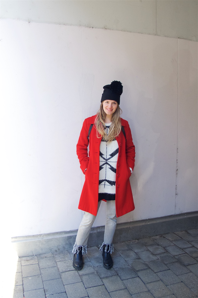 Red Coat. Fashion and Style Blog Girl from Heartfelt Hunt. Girl with blonde, long hair wearing a red coat, black and white oversized sweater, diy fringe jeans, dress, diy pompom beanie and boots.