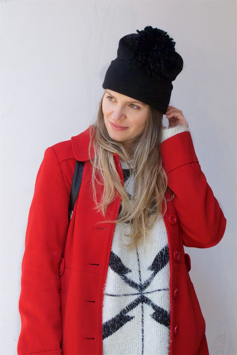 Red Coat. Fashion Blogger Girl by Style Blog Heartfelt Hunt. Girl with blond, long hair wearing a red coat, black and white oversized sweater, diy fringe jeans, dress, diy pompom beanie and boots.
