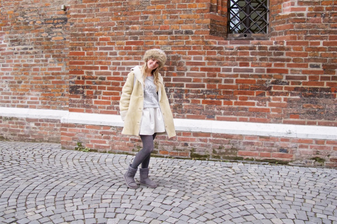 Russian Winter. Fashion Blogger Girl by Style Blog Heartfelt Hunt. Girl with blond loose curls wearing a sweater, brocade skirt, shearling jacket, faux fur beanie, backpack and Ugg boots.