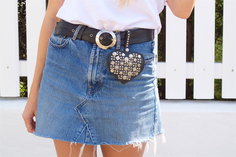 Studded Accessories. Fashion Blogger Girl by Style Blog Heartfelt Hunt. Girl with blond hair and a scarf hairstyle wearing studded boots, studded heart bag, Ray-Ban sunglasses, volant top, denim skirt and a belt.