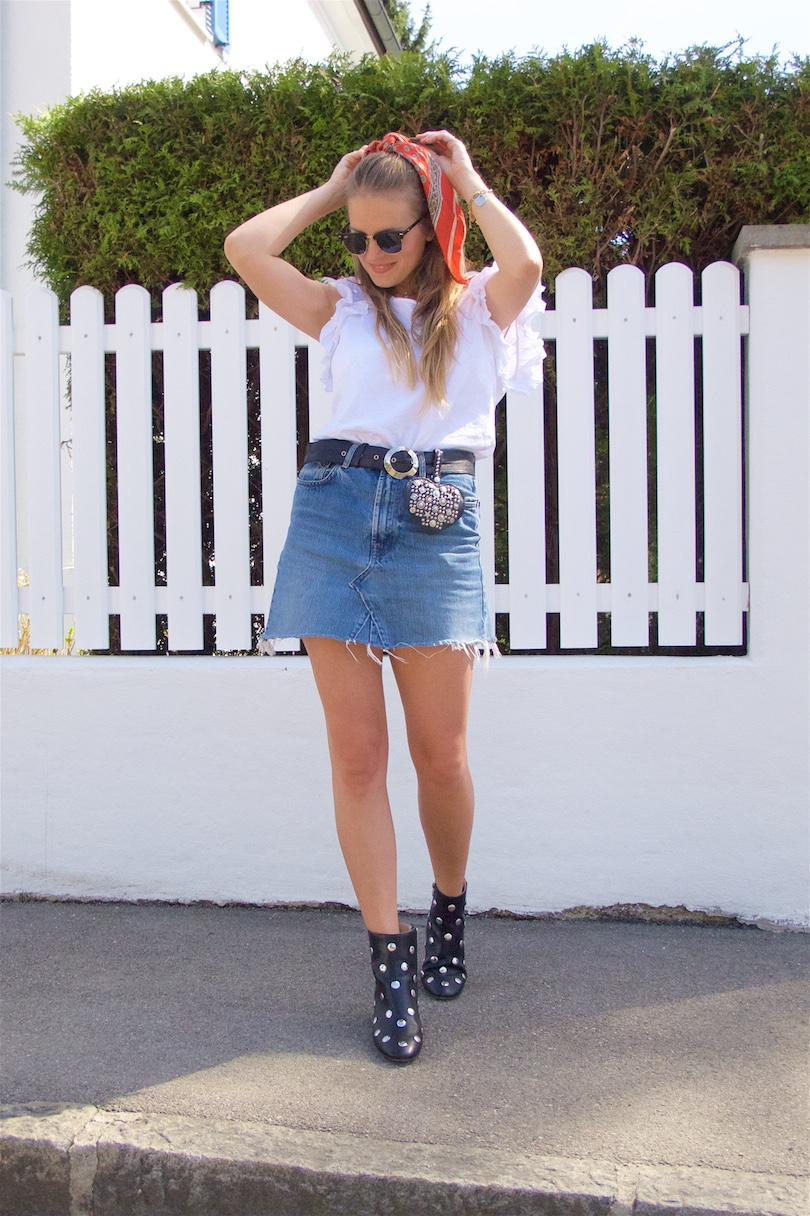 Studded Accessories. Fashion and Style Blog Girl from Heartfelt Hunt. Girl with blonde hair and a scarf hairstyle wearing studded boots, studded heart bag, Ray-Ban sunglasses, volant top, denim skirt and a belt.