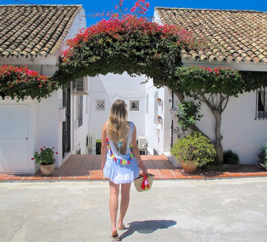 Tassels and Bougainvilleas. Fashion Blogger Girl by Style Blog Heartfelt Hunt. Girl with blond, long hair wearing a backless tassel top, basket bag with tassels, round sunglasses, denim shorts and sandals.