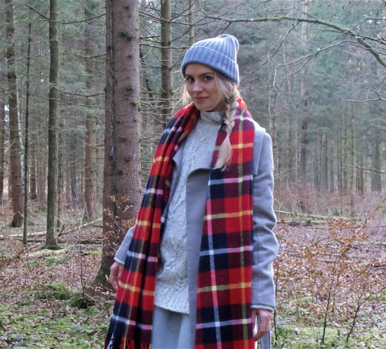 Winter Woods. Fashion Blogger Girl by Style Blog Heartfelt Hunt. Girl with blond fishtail braid wearing a heavy knit sweater, flared skirt, coat, pompom beanie, plaid scarf and Ugg boots.