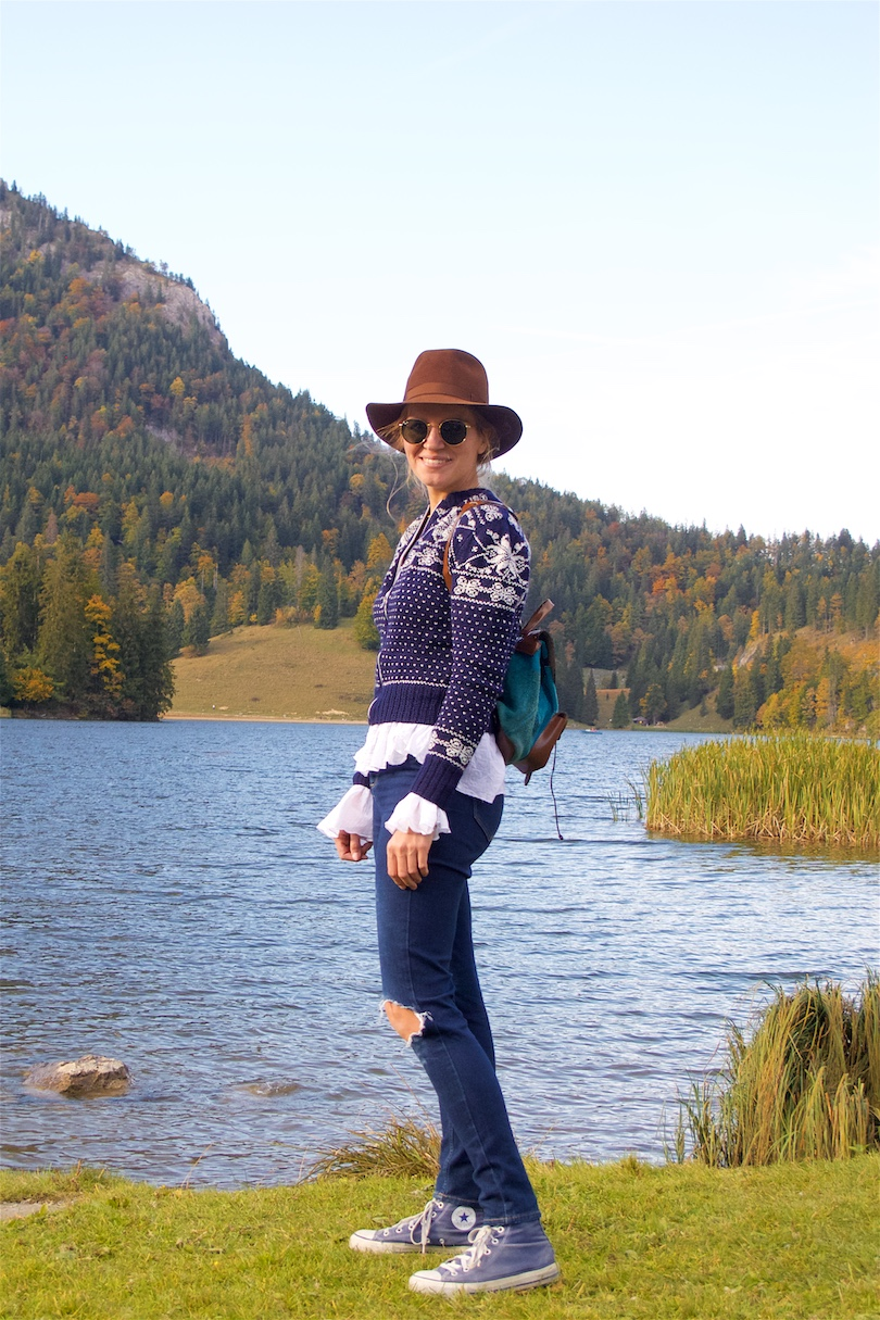 A Day In The Mountains. Fashion and Style Blog Girl from Heartfelt Hunt. Girl with blonde braid wearing a norwegian sweater, blouse with trumpet sleeves, destroyed denim jeans, hat, Ray-Ban sunglasses, backpack and Converse sneakers.