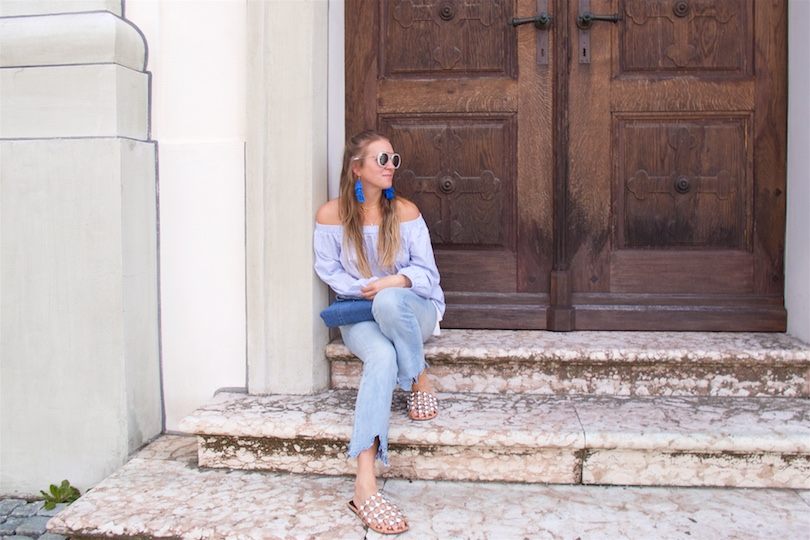 All Things Blue. Fashion and Style Blog Girl from Heartfelt Hunt. Girl with blonde half-up half-down hairstyle wearing a blue striped off shoulder blouse, blue destroyed jeans, blue diy denim bag, blue diy tassel earrings and studded sandals.