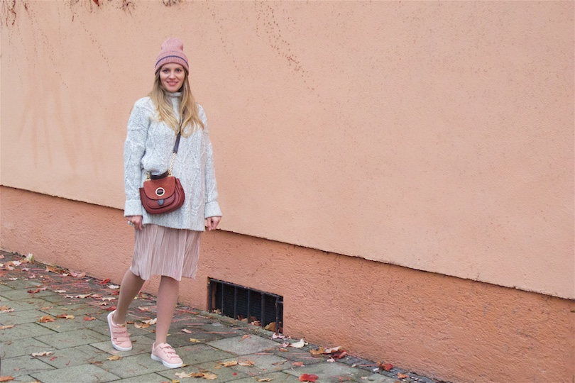 Autumnal Blush. Fashion Blogger Girl by Style Blog Heartfelt Hunt. Girl with blond, long hair wearing a blush pleated dress, heavy knit sweater, blush beanie, Michael Kors bag and blush sneakers.