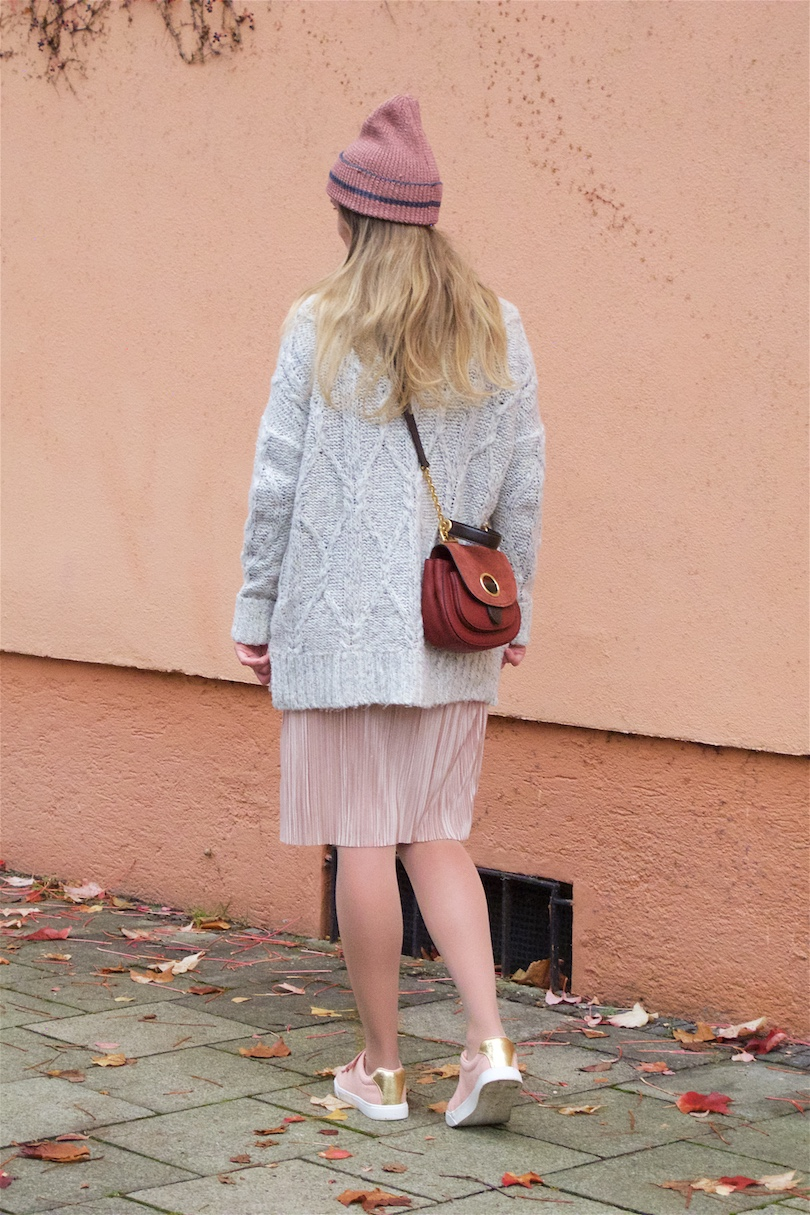 Autumnal Blush. Fashion and Style Blog Girl from Heartfelt Hunt. Girl with blonde, long hair wearing a blush pleated dress, heavy knit sweater, blush beanie, Michael Kors bag and blush sneakers.