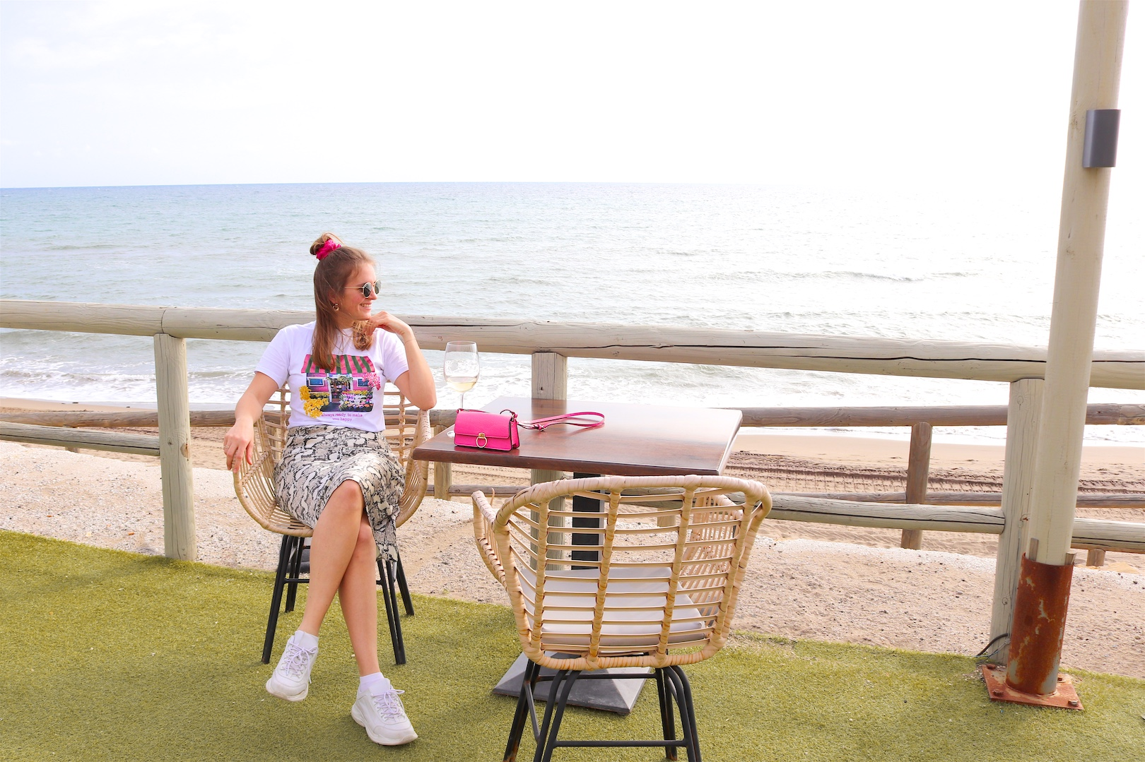 Beach Lunch. Fashion and Style Blog Girl from Heartfelt Hunt. Girl with blonde half-up half-down messy bun and pink scrunchie wearing a graphic tee, snake print skirt, Ray-Ban sunglasses, pink mini bag and chunky sneakers.