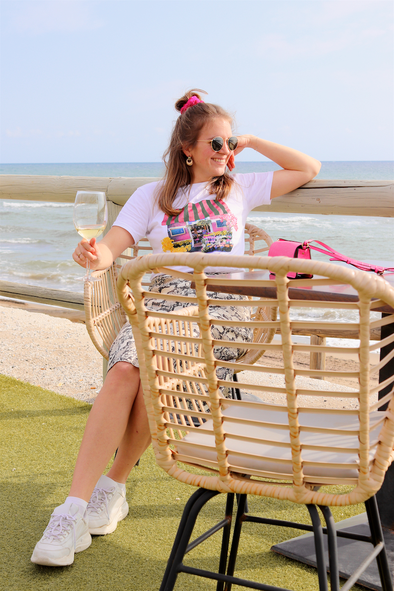 Beach Lunch. Fashion Blogger Girl by Style Blog Heartfelt Hunt. Girl with blond half-up half-down messy bun and pink scrunchie wearing a graphic tee, snake print skirt, Ray-Ban sunglasses, pink mini bag and chunky sneakers.