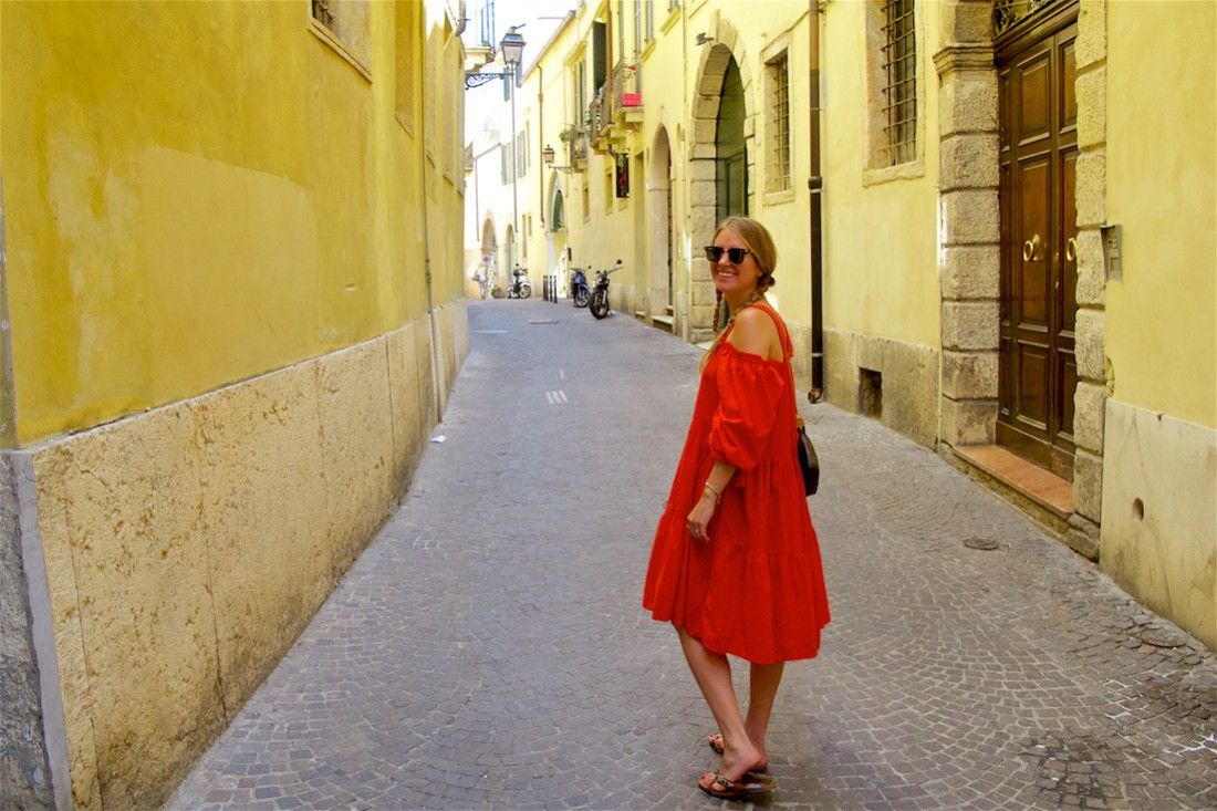 Beautiful Verona. Fashion Blogger Girl by Style Blog Heartfelt Hunt. Girl with two blond pigtail braids wearing an off-shoulder dress, Ray-Ban sunglasses, Louis Vuitton bag and sandals.
