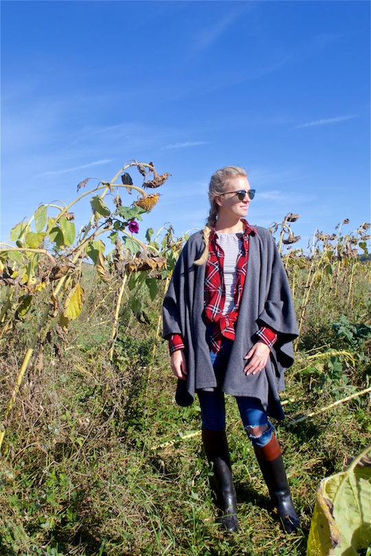 Beauty of Nature. Fashion and Style Blog Girl from Heartfelt Hunt. Girl with blonde dutch braid wearing a cape, plaid shirt, striped top, destroyed jeans, Ray-Ban sunglasses and boots.