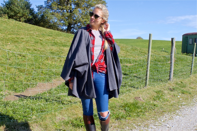 Beauty of Nature. Fashion Blogger Girl by Style Blog Heartfelt Hunt. Girl with blond dutch braid wearing a cape, plaid shirt, striped top, destroyed jeans, Ray-Ban sunglasses and boots.