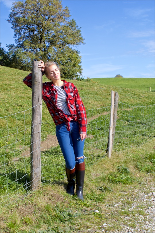 Beauty of Nature. Fashion Blogger Girl by Style Blog Heartfelt Hunt. Girl with blond dutch braid wearing a plaid shirt, striped top, destroyed jeans, Ray-Ban sunglasses and boots.