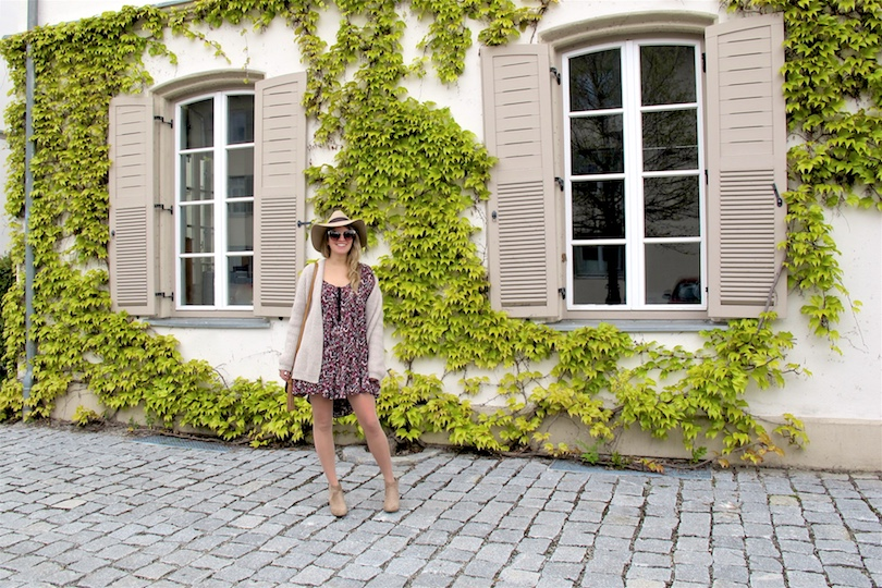 Beige Floral Dress. Fashion Blogger Girl by Style Blog Heartfelt Hunt. Girl with blond, loose curls wearing a beige cardigan, floral dress, floppy hat, tassel bag and beige boots.