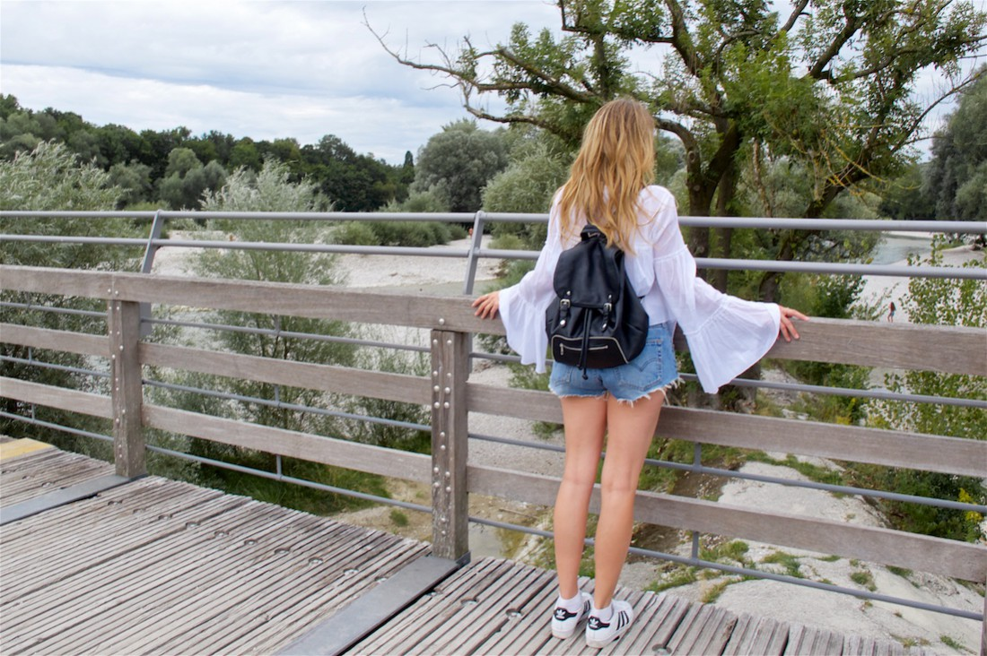 Bell Sleeve Blouse. Fashion Blogger Girl by Style Blog Heartfelt Hunt. Girl with blond beach waves wearing a white bell sleeve blouse, denim shorts, backpack and adidas sneakers.