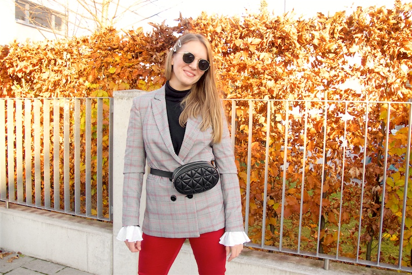 Belt Bag. Fashion and Style Blog Girl from Heartfelt Hunt. Girl with blonde hair wearing a belt bag, checked blazer, black turtleneck sweater, blouse with trumpet sleeves, red jeans, round Ray-Ban sunglasses and white boots.