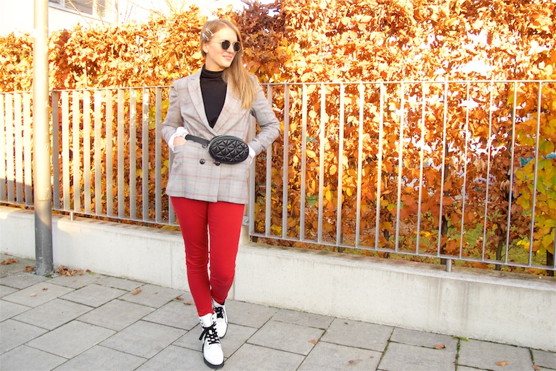 Belt Bag. Fashion Blogger Girl by Style Blog Heartfelt Hunt. Girl with blond hair wearing a belt bag, checked blazer, black turtleneck sweater, blouse with trumpet sleeves, red jeans, round Ray-Ban sunglasses and white boots.