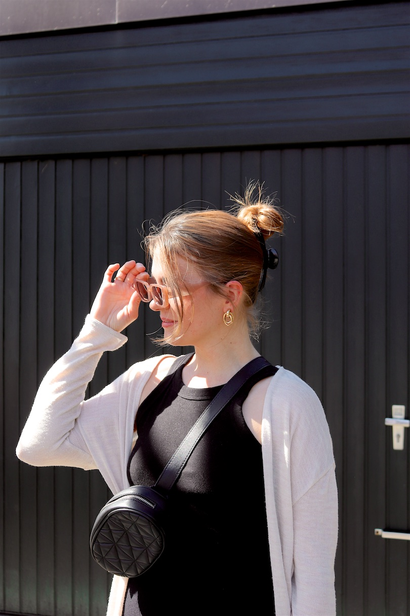 Black Spring Love. Fashion Blogger Girl by Style Blog Heartfelt Hunt. Girl with blond hair with a hair claw clip wearing a long cardigan, black top, black culotte, slim sunglasses, belt bag and mules.