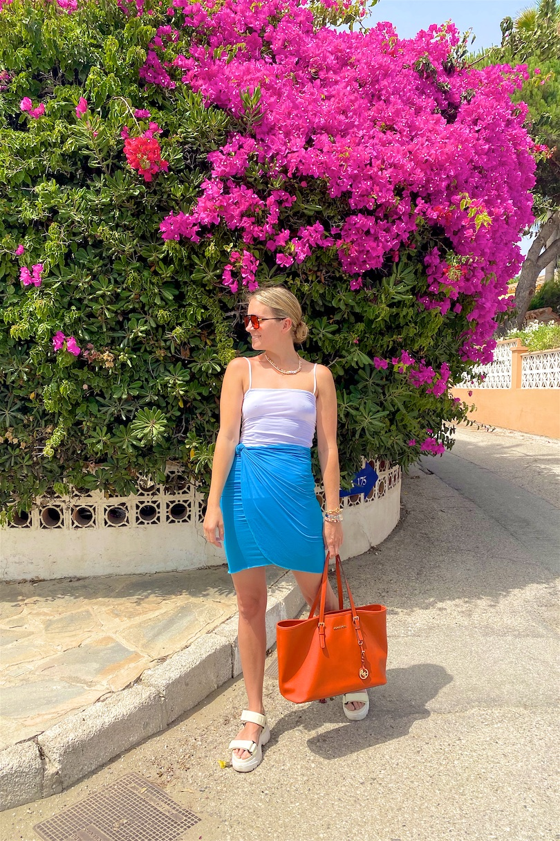 Blue Orange. Fashion Blogger Girl by Style Blog Heartfelt Hunt. Girl with blond, low bun wearing a blue skirt, white top, orange sunglasses, orange Michael Kors bag and chunky sandals.