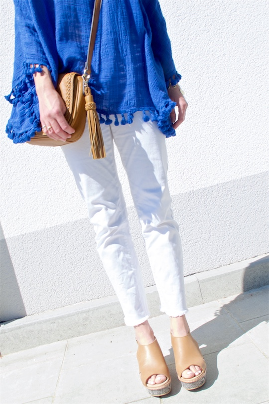 Blue Tassels. Fashion and Style Blog Girl from Heartfelt Hunt. Girl with two braids wearing a top with blue tassels, white jeans, bag with tassel and wedges.