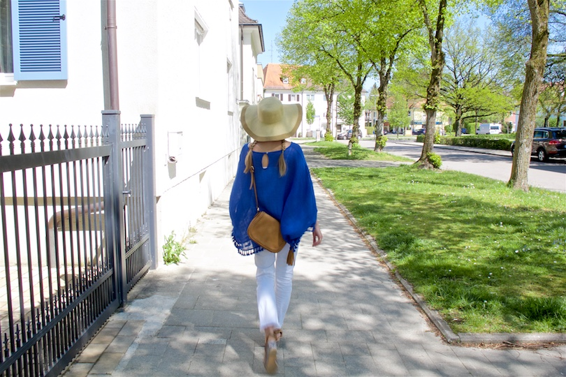 Blue Tassels. Fashion and Style Blog Girl from Heartfelt Hunt. Girl with two braids wearing a top with blue tassels, white jeans, bag with tassel, wedges and a straw hat.