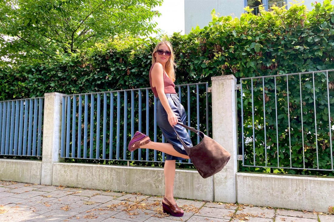 Brown Faux Leather. Fashion Blogger Girl by Style Blog Heartfelt Hunt. Girl with blond hair wearing a brown structured top, faux leather shorts, edgy sunglasses, brown bag and brown heels.