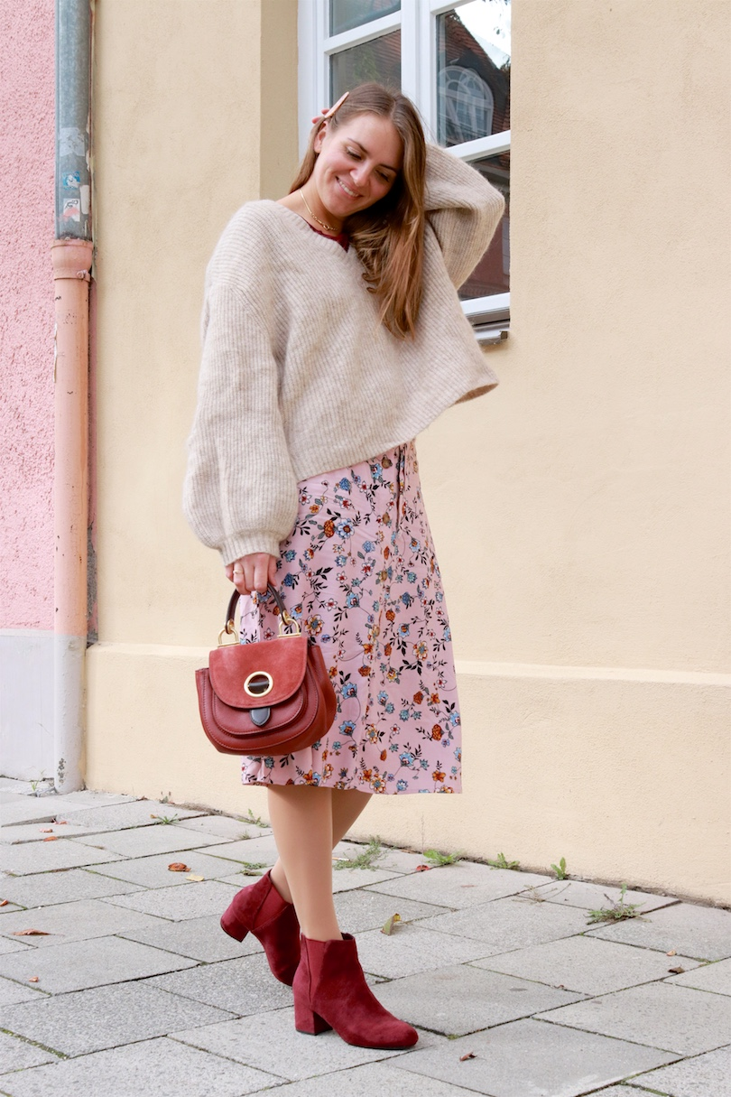 Burgundy Accessories. Fashion Blogger Girl by Style Blog Heartfelt Hunt. Girl with blond hair and a pink tortoiseshell hair clip wearing a chunky sweater, floral skirt, burgundy T-shirt, burgundy bag and burgundy boots.