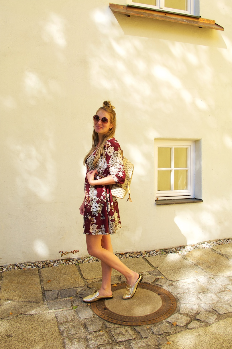 Burgundy Flower Dress. Fashion and Style Blog Girl from Heartfelt Hunt. Girl with blonde half-up half-down bun wearing a burgundy flower dress, round sunglasses, Michael Kors backpack and mules.