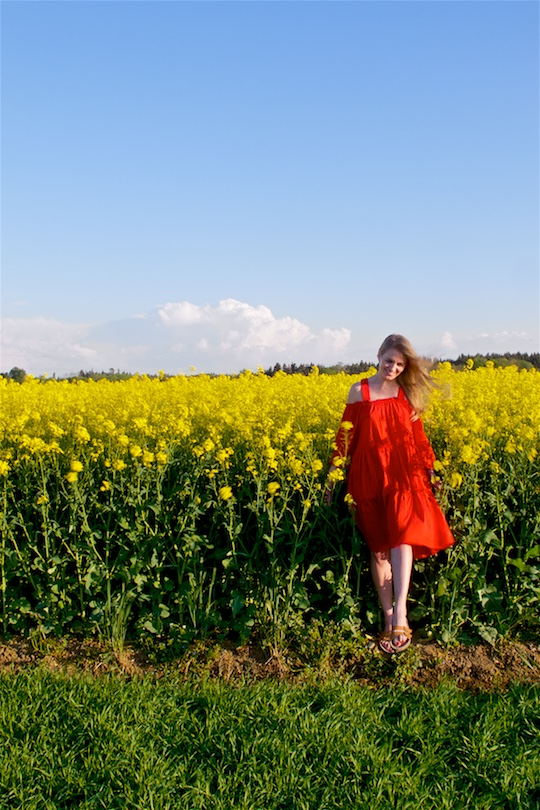 Canola Field. Fashion and Style Blog Girl from Heartfelt Hunt. Girl wearing a red off-shoulder dress and sandals.