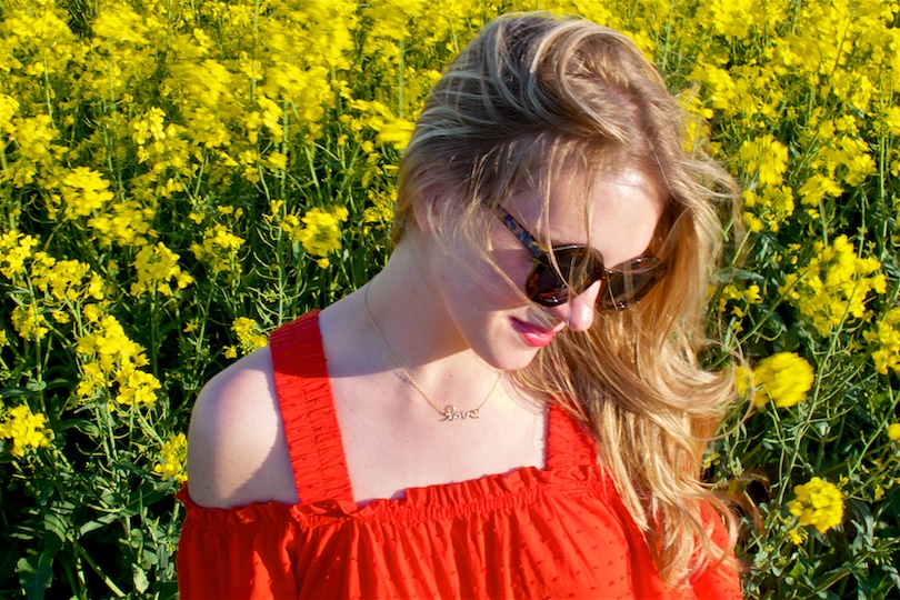 Canola Field. Fashion and Style Blog Girl from Heartfelt Hunt. Girl wearing a red off-shoulder dress, sunglasses and sandals.