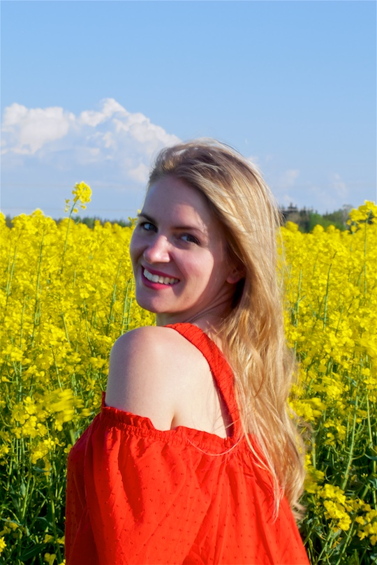 Canola Field. Fashion Blogger Girl by Style Blog Heartfelt Hunt. Girl wearing a red off-shoulder dress and sandals.