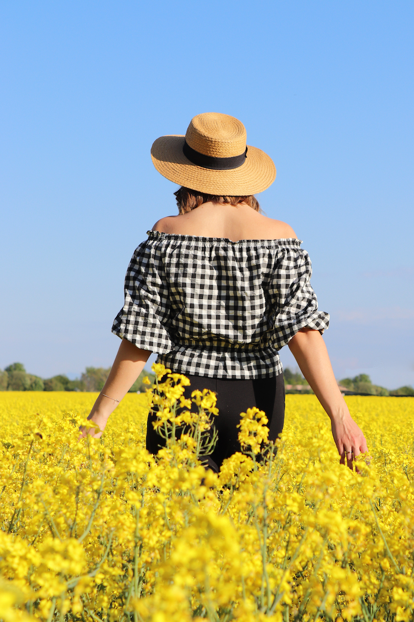 Canola Love. Fashion and Style Blog Girl from Heartfelt Hunt. Girl with blonde beach waves wearing an off-shoulder gingham blouse, black culotte, straw hat and straw bag.