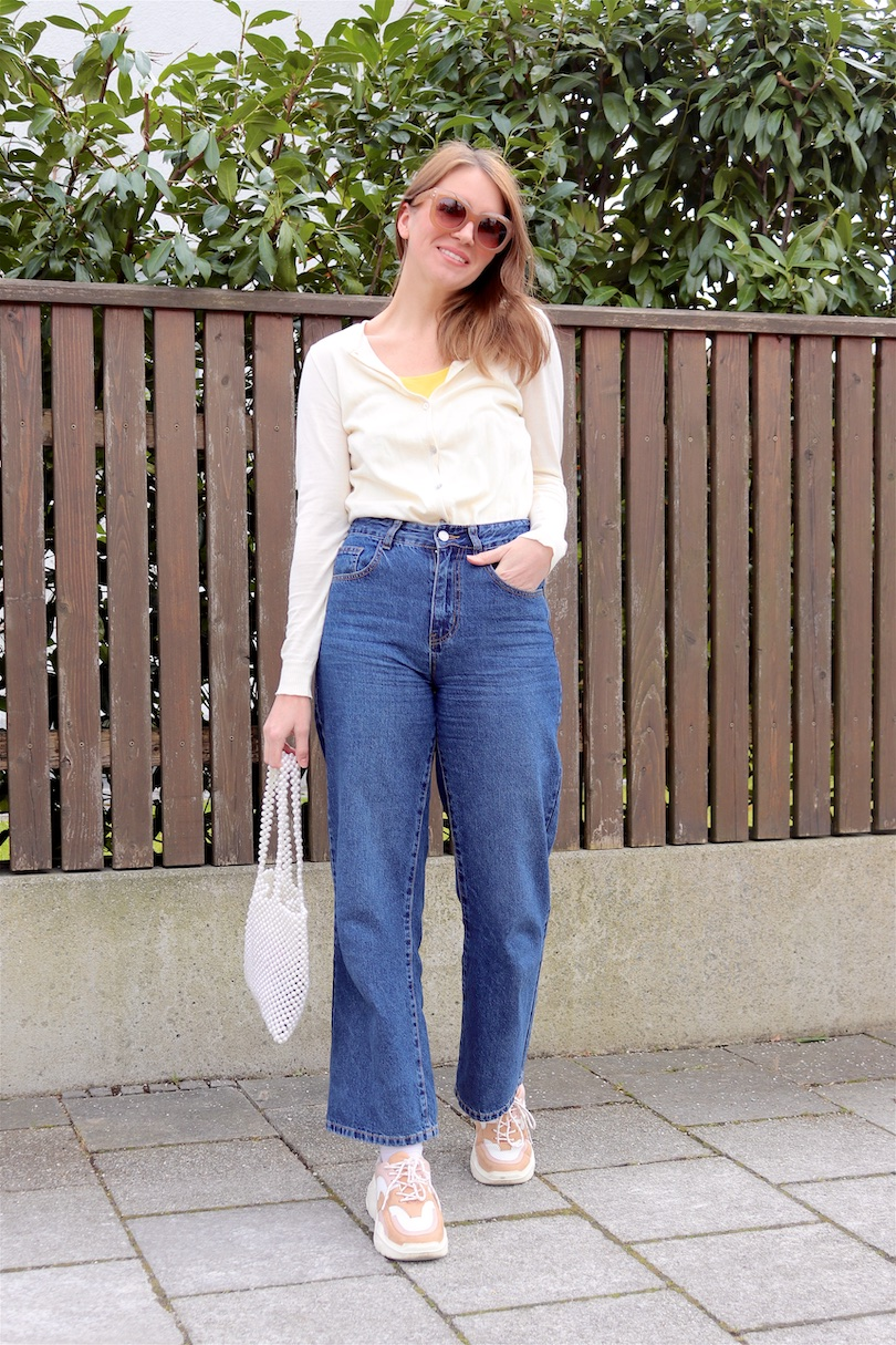 Casual Spring Look. Fashion Blogger Girl by Style Blog Heartfelt Hunt. Girl with blond hair wearing a cardigan, yellow top, 70s sunglasses, wide leg jeans, pearl bag and chunky sneakers.